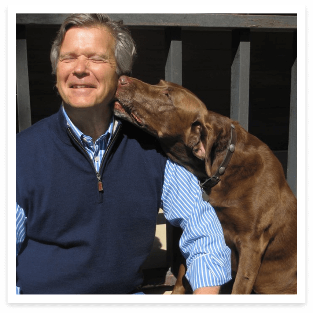 Man with a brown dog licking his cheek